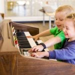 kids experimenting with a piano