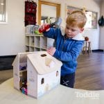 boy hammering the toy house